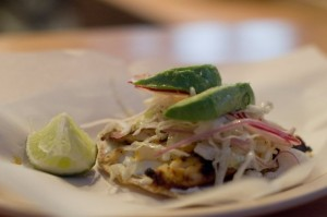 Tostada de Pescado: wood grilled basa, cucumber-onion spread, radish, cabbage, avocado. $3.